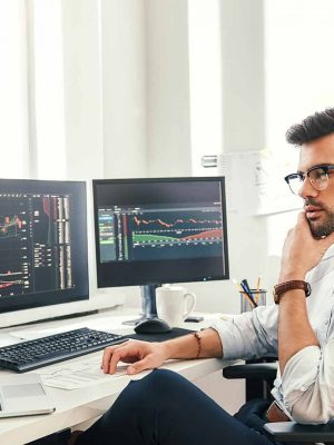 Trader in eyeglasses and formal wear working with laptop while sitting in his office in front of computer screens with trading charts. Hero image for Day Trading article.